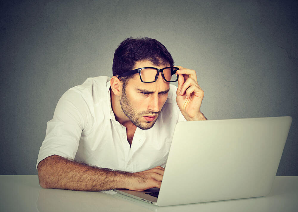Man squinting to read laptop