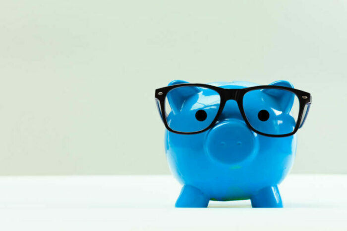Blue piggy bank wearing glasses