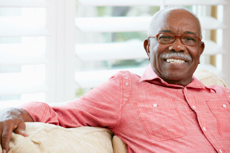 Senior male sitting on couch, wearing glasses, smiling at camera