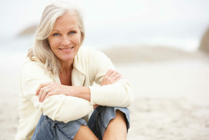 Senior woman sitting on the beach smiling at camera