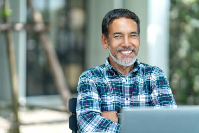 Middle-aged man in front of laptop, smiling