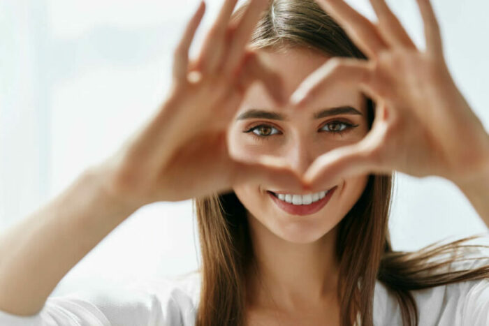 Young woman making a heart with her hands