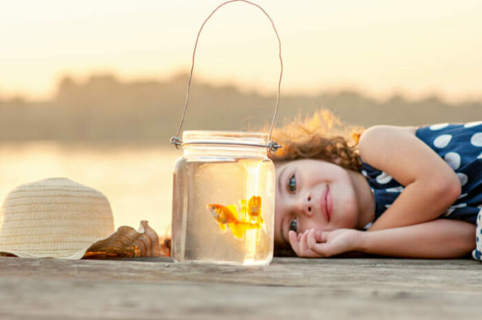 Little girl laying on a dock looking at goldfish in a jar.