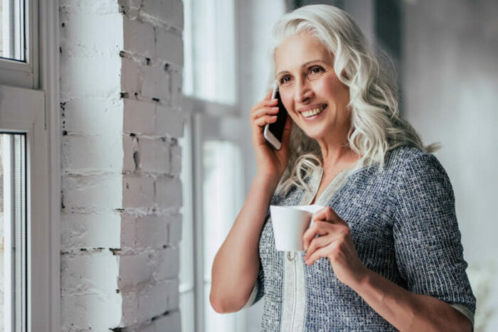 Senior woman on phone holding coffee cup