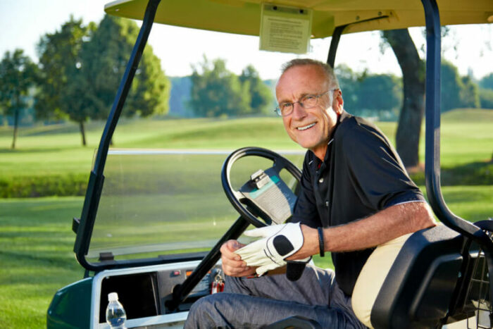 Senior man in golf cart smiling.